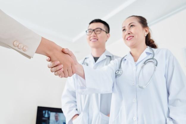 Pacjent i lekarze, ściskając ręce