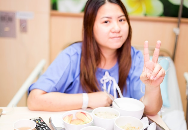 Pacjent kciuki ok znak i uśmiech podczas odpoczynku na łóżku szpitalnym