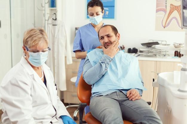 Pacjent kładący rękę na policzku pokazujący ból zęba, skarżący się na ból zęba