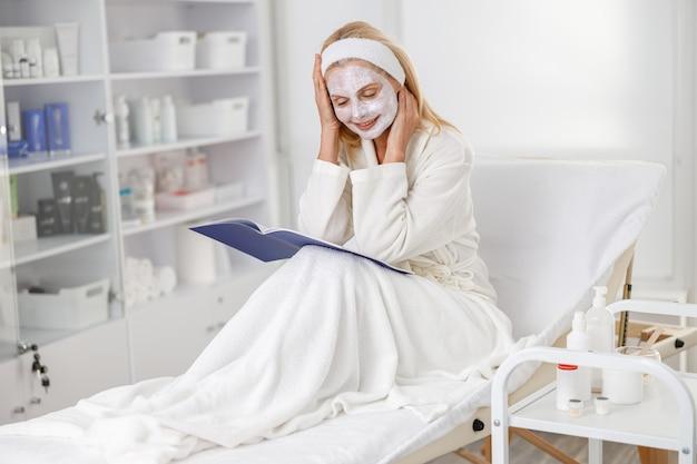 Pacjent leżący na kanapie czeka na efekty zabiegu pielęgnacyjnego w trakcie czytania katalogu.