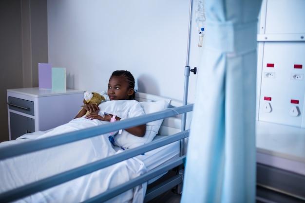 Pacjent leżący na łóżku z misiem