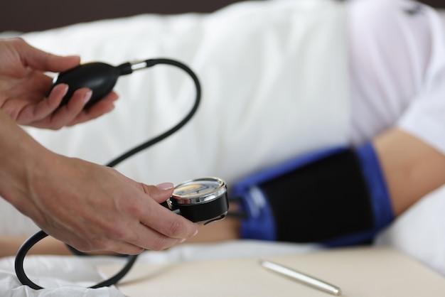 Pacjent leży na łóżku, mierzy się ciśnienie krwi. koncepcja objawy wysokiego lub niskiego ciśnienia krwi