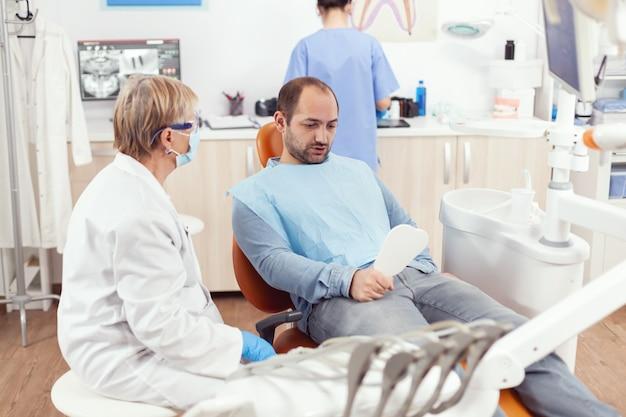 Pacjent mężczyzna patrzący w lustro po zakończeniu zabiegu stomatologicznego przez zespół stomatologiczny podczas zabiegu stomatologicznego