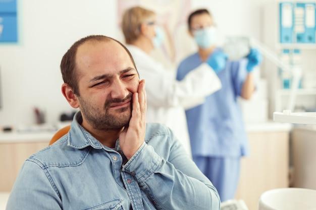 Pacjent mężczyzna skarży się na ból zębów, czekając na lekarza stomatologa, który sprawdzi ból zęba