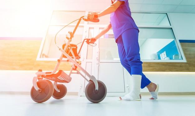 Pacjent na rollatorze z hamulcami ręcznymi poruszającymi się w szpitalu