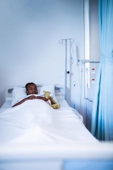 Pacjent odpoczywa na łóżku przy szpitalem
