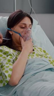 Pacjent odpoczywający w łóżku z chorobą układu oddechowego, podczas gdy lekarze monitorują puls serca za pomocą oksymetru...