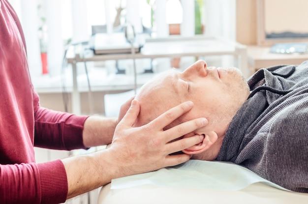 Pacjent płci męskiej poddawany terapii czaszkowo-krzyżowej, leżący na stole do masażu w poradni osteopatycznej cst, osteopatii i terapii manualnej