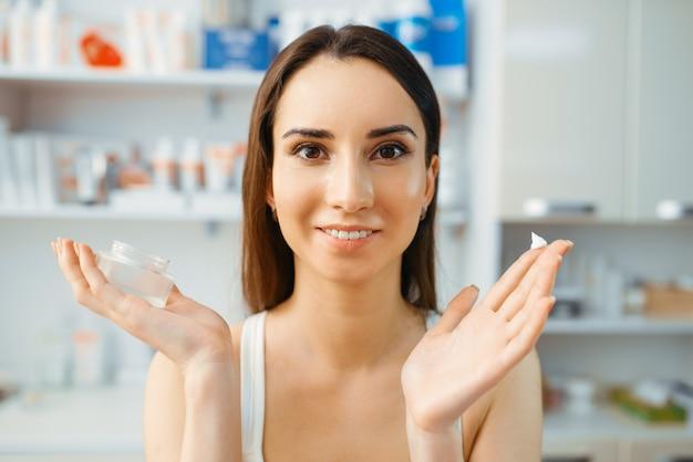 Pacjent pokazuje krem na palcu, gabinet kosmetyczki