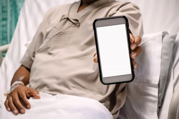 Pacjent pokazuje monitorowi smartphone w szpitalu