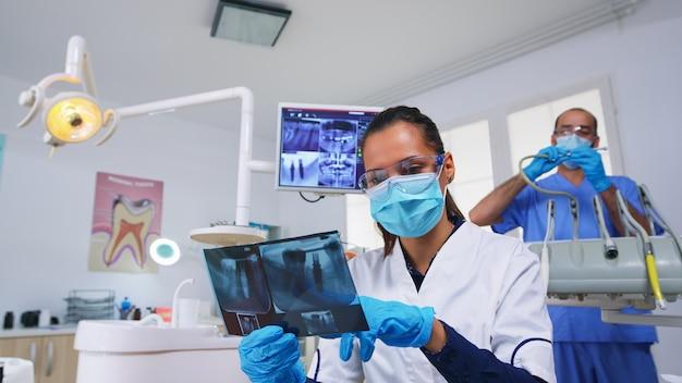 Pacjent pov w gabinecie dentystycznym planuje kroki chirurgii jamy zębów, dentysta wskazując na zdjęcie rentgenowskie. lekarz stomatolog w masce ochronnej i rękawiczkach, pracujący w nowoczesnej klinice stomatologicznej