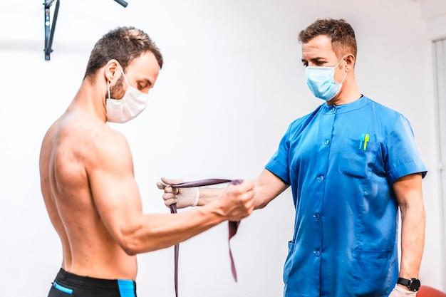 Pacjent pracujący z ramieniem fizjoterapeuty. fizjoterapia ze środkami ochronnymi przeciwko pandemii koronawirusa, covid-19. osteopatia, terapeutyczny chiromasaż