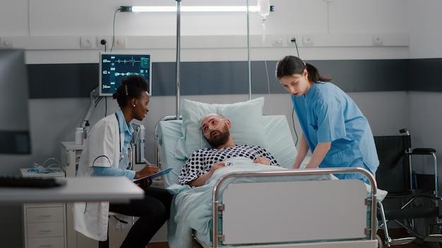 Pacjent rozmawia z lekarzami siedząc w łóżku podczas powrotu do zdrowia