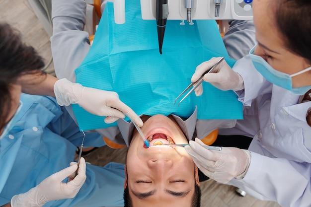 Pacjent siedzi na fotelu dentystycznym z szeroko otwartymi ustami, gdy dentysta sprawdza zęby i szuka ubytku, choroby dziąseł i płytki nazębnej
