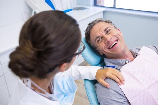 Pacjent siedzi na krześle patrząc na dentystę w przychodni