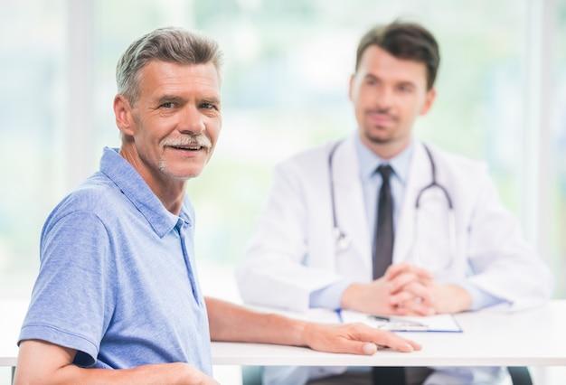 Pacjent siedzi w biurze lekarzy i patrząc na kamery.