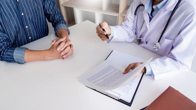 Pacjent słucha uważnie męskiego lekarza wyjaśniającego objawy pacjenta lub zadającego pytanie podczas wspólnej dyskusji na temat dokumentacji