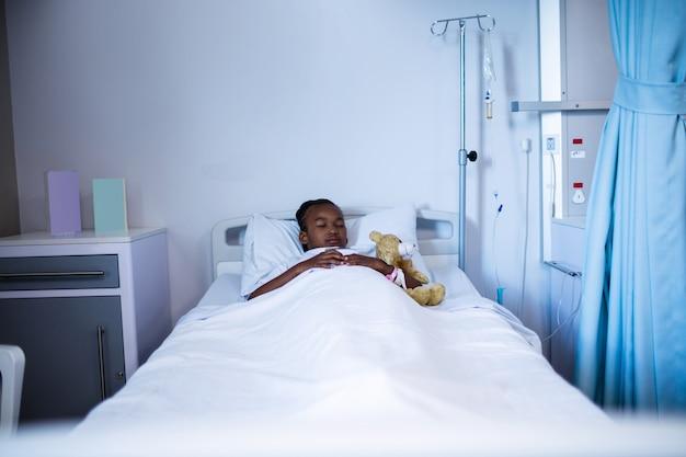 Pacjent śpi z misiem na łóżku