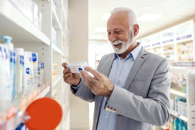 Pacjent w aptece czyta oświadczenia na opakowaniu leku. starszy mężczyzna z uśmiechem w eleganckim garniturze trzyma paczkę leków i czyta oświadczenie oraz datę ważności