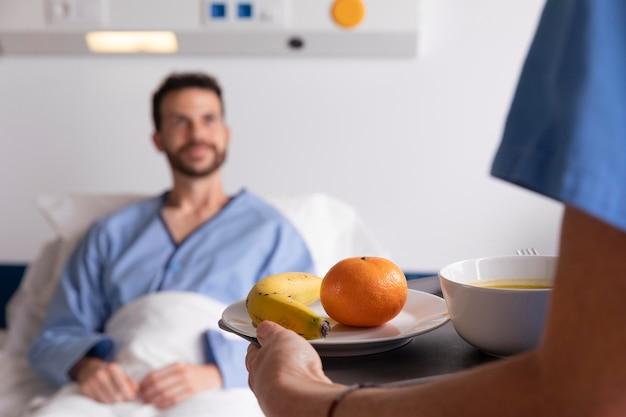 Pacjent w łóżku rozmawia z pielęgniarką