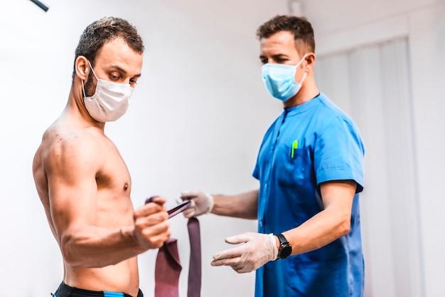 Pacjent w masce z ramieniem ćwiczy z fizjoterapeutą. fizjoterapia ze środkami ochronnymi przeciwko pandemii koronawirusa, covid-19. osteopatia, terapeutyczny chiromasaż
