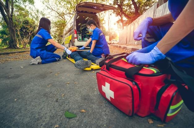 Pacjent w nagłym wypadku cierpi na głowie leżąc na noszach. szkolenie z pierwszej pomocy i przemieszczanie pacjenta w nagłym wypadku. sanitariusz przenosi pacjenta do ambulansu. wybierz skup się na apteczce.