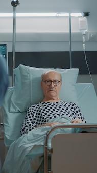 Pacjent w podeszłym wieku czeka na wyniki w łóżku na oddziale szpitalnym
