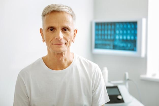 Pacjent w podeszłym wieku. pozytywny miły starszy mężczyzna patrzy na ciebie i uśmiecha się będąc w gabinecie lekarskim