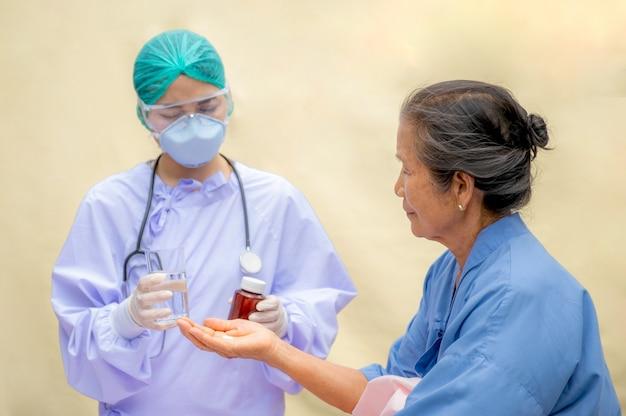 Pacjent w podeszłym wieku w łóżku przyjmuje lek podany przez lekarza