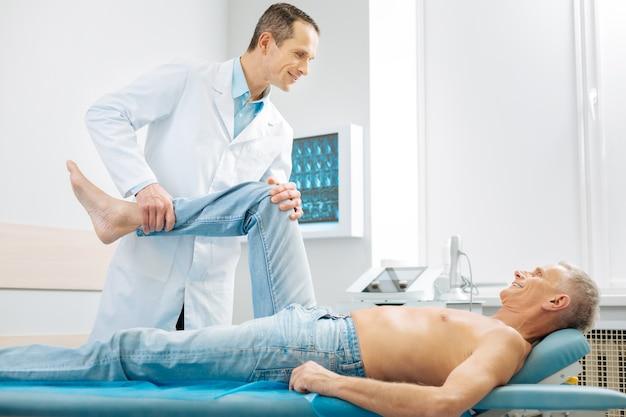 Pacjent w podeszłym wieku. wesoły, zachwycony starszy mężczyzna leżący na łóżku do masażu i uśmiechnięty, ciesząc się procesem terapii