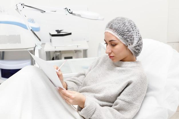 Pacjent w recepcji kosmetyczki wypełnia kartę pacjenta