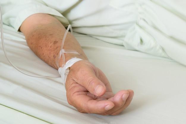 Pacjent w szpitalu z roztworem soli dożylnie, w azjatyckiej ręce starszego mężczyzny