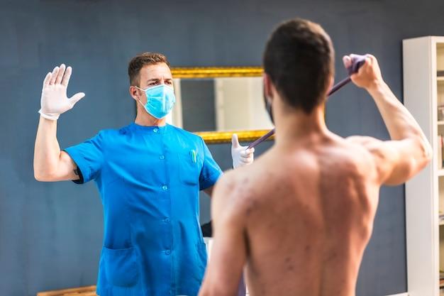 Pacjent wykonujący ćwiczenia ramion z fizjoterapeutą. fizjoterapia ze środkami ochronnymi przeciwko pandemii koronawirusa, covid-19. osteopatia, terapeutyczny chiromasaż
