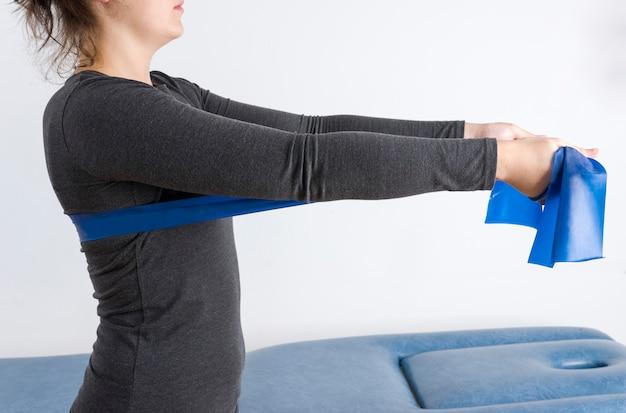 Pacjent wykonuje terapię za pomocą elastycznej opaski wzmacniającej