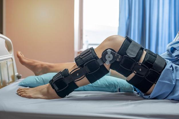 Pacjent z bandażem kompresyjnym orteza kolana wspiera uraz na łóżku w szpitalu pielęgniarskim. opieka zdrowotna i wsparcie medyczne.