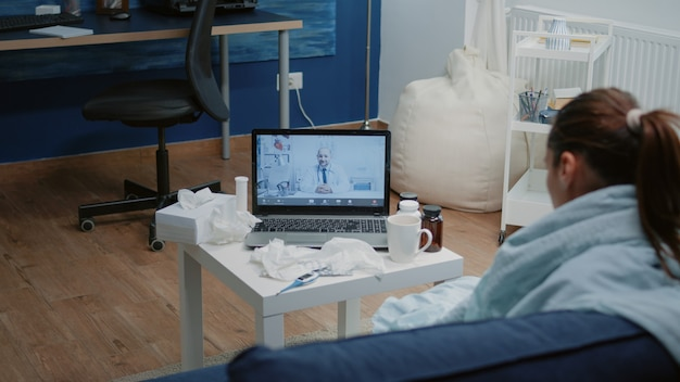 Pacjent z chorobą korzystający z wideorozmowy do telemedycyny na laptopie