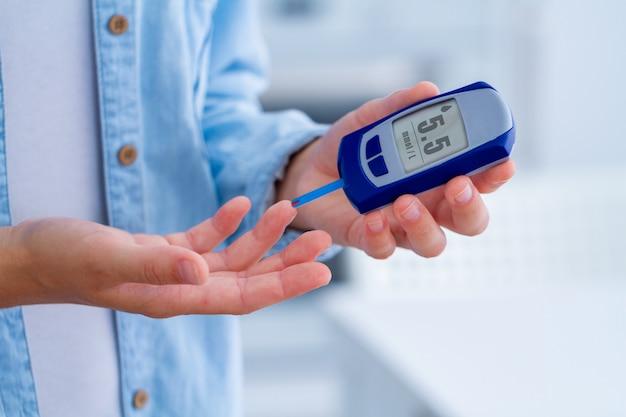 Pacjent z cukrzycą mierzy poziom glukozy we krwi za pomocą glukometru w domu. kobieta kontroluje cukrzycę