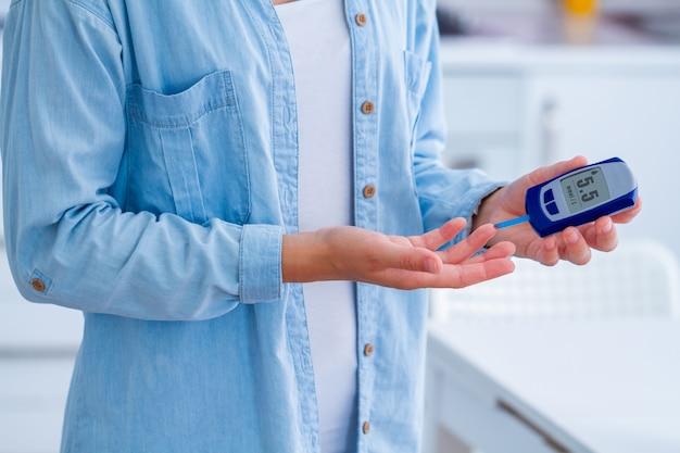Pacjent z cukrzycą mierzy poziom glukozy we krwi za pomocą glukometru w domu. kobieta z cukrzycą, kontrolować i analizować poziom glukozy