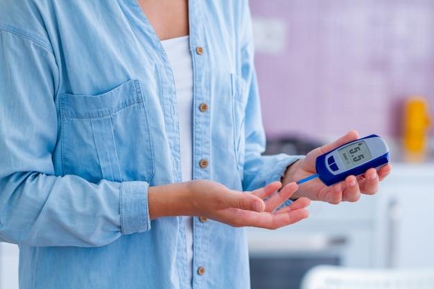 Pacjent z cukrzycą mierzy poziom glukozy we krwi za pomocą glukometru w domu. kobieta z cukrzycą, kontrolować poziom glukozy