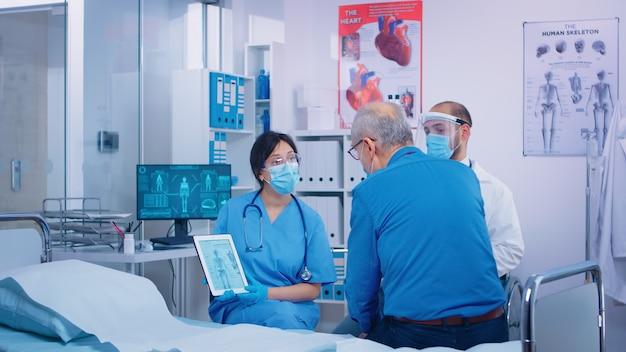Pacjent z osteoporozą otrzymuje konsultację lekarską od pielęgniarki i lekarza, patrząc na cyfrowy tablet, w nowoczesnym szpitalu lub przychodni. krzywica, osteomalacja osteogeneza imperfecta lub marmurowa kość kostna