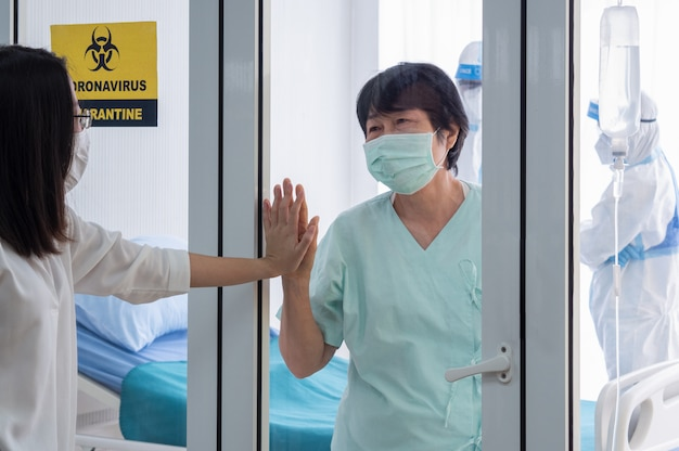Pacjent z zakażeniem koronawirusem w sali kwarantanny podciśnieniowej ze znakiem ostrzegawczym kwarantanny w szpitalu czuje się szczęśliwy i wesoły z członkiem rodziny.