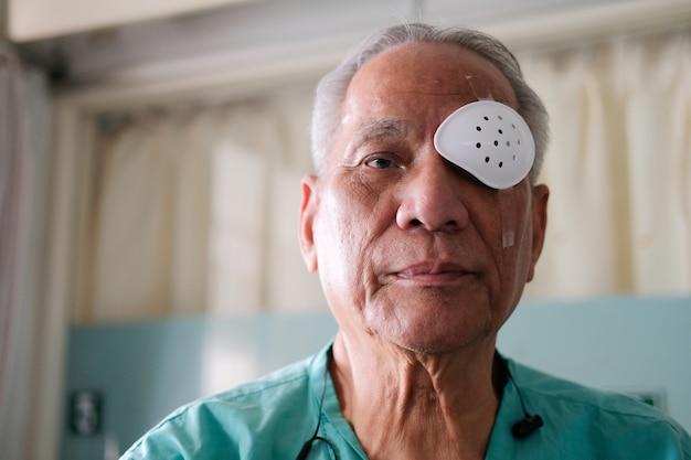 Pacjent zakrywający oko tarczą ochronną po operacji zaćmy w szpitalu