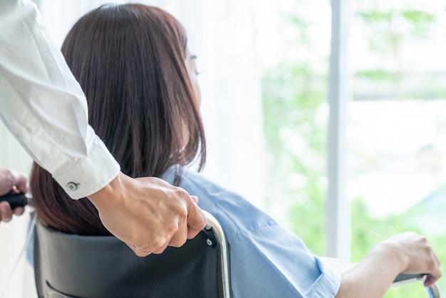 Pacjentka na wózku inwalidzkim ze starszym lekarzem