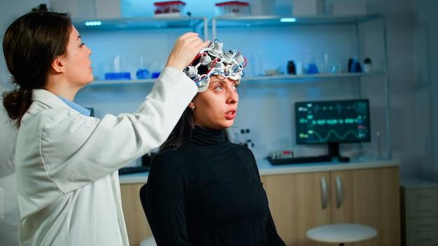 Pacjentka odwiedzająca profesjonalnego badacza medycznego w dziedzinie medycyny neurologicznej testująca funkcje mózgu za pomocą zestawu słuchawkowego eeg