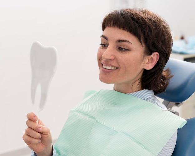 Pacjentka patrząca w lustro po zabiegu stomatologicznym