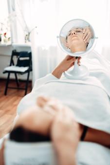 Pacjentka patrzy na swoją twarz przez lustro
