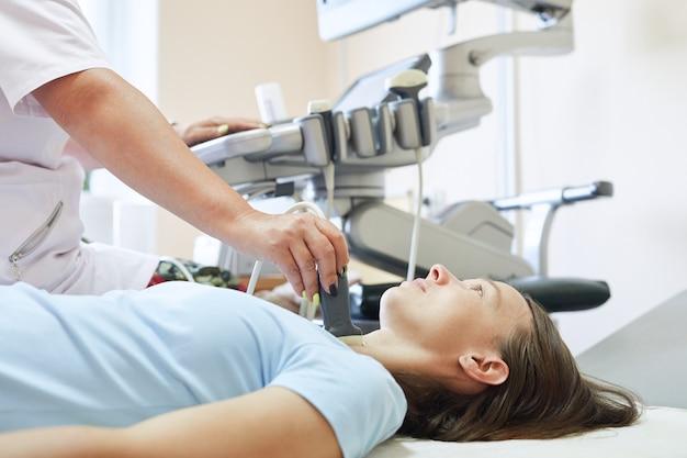 Pacjentka podczas badania usg tarczycy leżąca na kanapie w gabinecie lekarskim