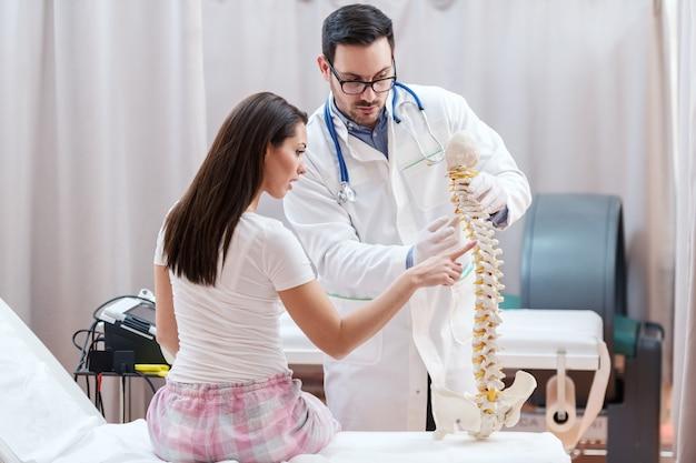 Pacjentka siedzi i pokazuje model kręgosłupa, w którym odczuwa ból.
