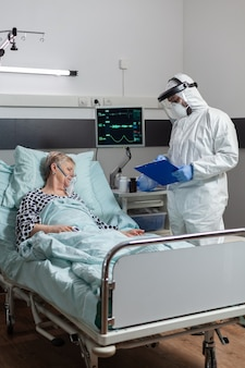 Pacjentka starsza kobieta leżąca nieprzytomna w łóżku szpitalnym podczas epidemii koronawirusa, oddychająca z pomocą maski tlenowej