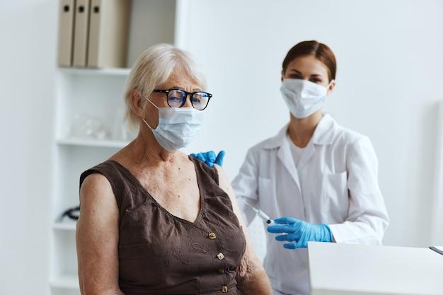 Pacjentka starsza kobieta siedząca obok paszportu pielęgniarki covid